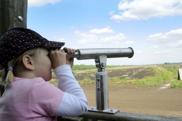 """Erlebnispfad """"moor-land-schaffen"""" - Mädchen blickt vom Aussichtsturm auf Moorlandschaft"""