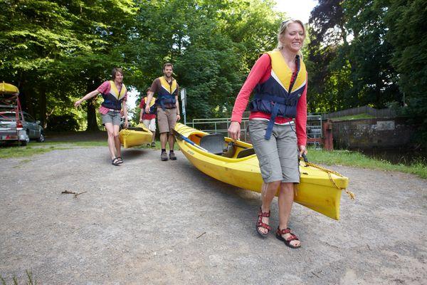 Paddeln auf Ems und Hase - Kanus werden zum Bootsanleger getragen