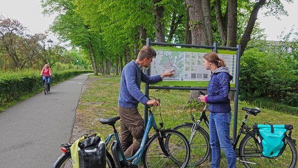Radfahrer vor Infotafel vom Fahrradknotennetz Emsland am Dortmund-Ems-Kanal in Meppen