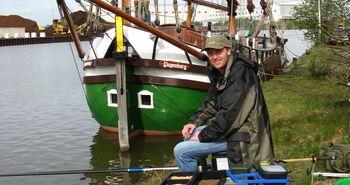 Mann beim Angeln vor Schiff