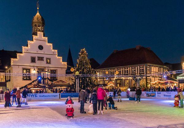 Weihnachtsmarkt in Lingen (Ems) – Blick auf Altes Rathaus, Alte Posthalterei und Eislaufbahn auf dem Marktplatz