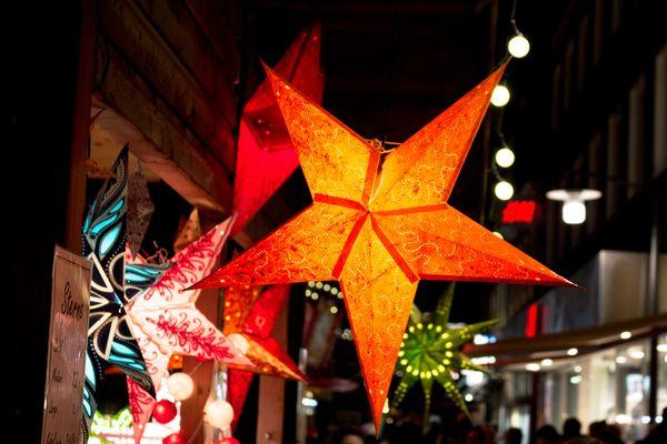 Adventszeit im Emsland – leuchtende Weihnachtssterne an Bude auf einem Weihnachtsmarkt