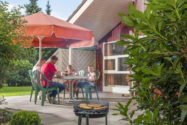 Familie beim Grillen auf der Terrasse vom Ferienhaus im Emsland-Urlaub