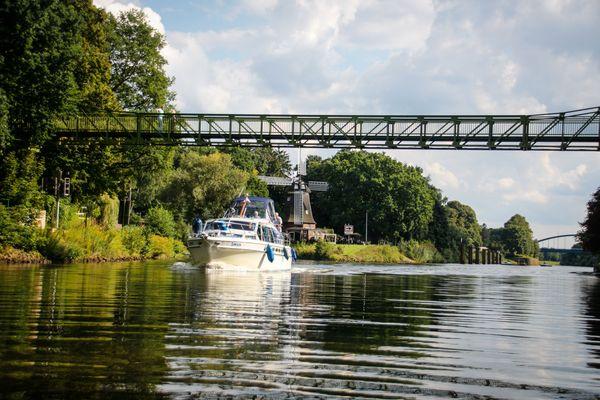 Sportboot unterwegs auf dem Dortmund-Ems-Kanal in Meppen, im Hintergrund ist die Höltingmühle zu sehen