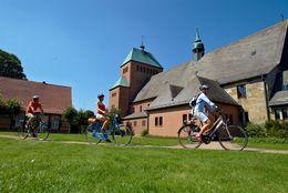 Radfahrer unterwegs auf der Pionierroute vor der Kirche St. Johannes Apostel in Wietmarschen