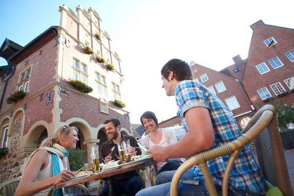 Gruppe isst im Rathaus-Café auf dem Marktplatz in Meppen