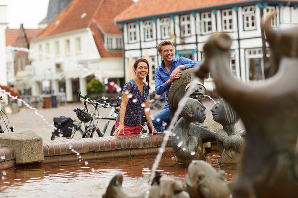 Radfahrer am Fabeltier-Brunnen auf dem Marktplatz in Lingen (Ems)