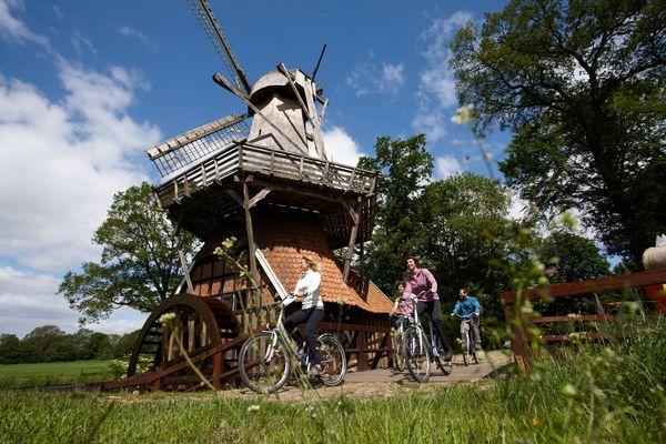 Hüvener Mühle - Radfahrer passieren die Mühle auf der Radtour entlang der Emsland-Route