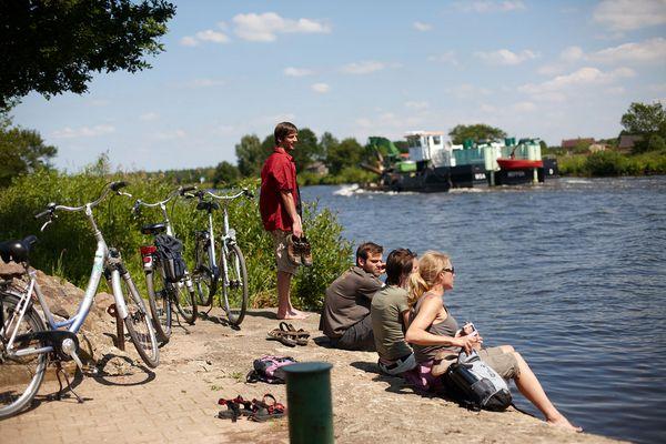 Radfahrer unterwegs auf der Emsland-Route pausieren an der Ems